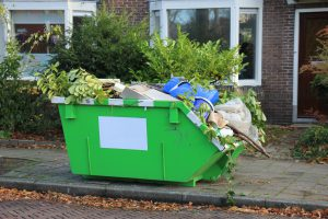 Small Green Skip Outside House
